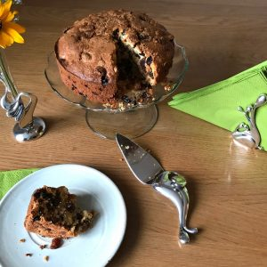 cake server with cake on a stand and bud bvase and serviette holder all set out on a wooden table