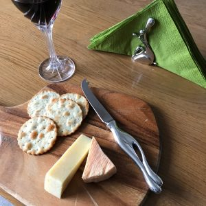 cheesknife on a board with cheese glass of wine and serviette holder