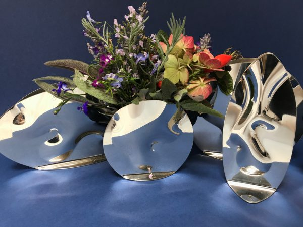 Pewter flow vases with flowers on a blue background