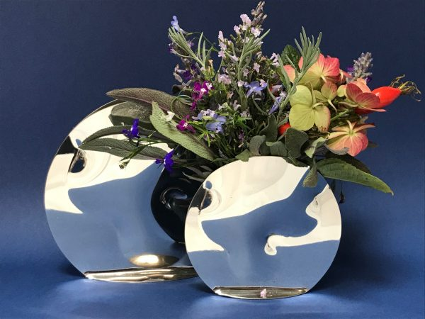 Round large and small vase small vase holding bunch of flowers